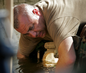 KENT SIEVERS/THE WORLD-HERALD - Elbow deep in poisonous flood water, Tom Brewer attaches a tow cable to an LAV stranded in debris in the parking lot of a strip mall in New Orleans East in 2005. Brewer led a five-state National Guard crew through the city's flooded streets in the aftermath of Hurricane Katrina.