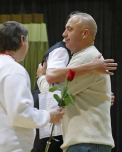 Teresa Prince - Tom Brewer hugs his son Travis after the parent's night ceremony at Elmwood-Murdock High School. Brewer watches most of his son's games on videos in Afghanistan.